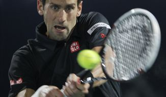 Novak Djokovic of Serbia returns the ball to Spain's Roberto Bautista Agut during the third day of the Dubai Tennis Championships in Dubai, United Arab Emirates, Wednesday, Feb. 26, 2014. (AP Photo/Kamran Jebreili)