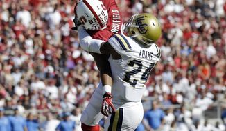 FILE - In this Oct. 19, 201,3 file photo, Stanford wide receiver Kodi Whitfield, left, makes a one-handed touchdown catch next to UCLA cornerback Ishmael Adams during an NCAA college football game in Stanford, Calif. Whitfield made one of the most incredible touchdown catches in college football last season in a win over UCLA that kept Stanford on track for a second straight Pac-12 Conference championship. If Whitfield has his way, he'll be breaking up catches like that next season. Whitfield is trying to transition from wide receiver to free safety this spring. (AP Photo/Marcio Jose Sanchez, file)
