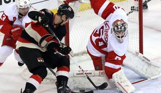 Detroit Red Wings goaltender Jonas Gustavsson (50) makes a pad save on Ottawa Senators' Zack Smith (15) during first period NHL hockey in Ottawa, Thursday, Feb. 27, 2014. (AP Photo/The Canadian Press, Fred Chartrand)