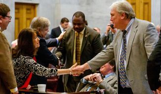 House Democratic Caucus Chairman Mike Turner, right, shakes hands with Rep. Sheila Butt, R-Columbia, on the House floor in Nashville, Tenn., on Thursday. Feb. 27, 2014. Turner, D-Nashville, announced he won't seek re-election this year. (AP Photo/Erik Schelzig)