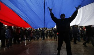 Pro-Russian demonstrators march with a huge Russian flag during a protest in front of a local government building in Simferopol, Crimea, Ukraine, Thursday, Feb. 27, 2014. Ukraine's acting interior minister says Interior Ministry troops and police have been put on high alert after dozens of men seized local government and legislature buildings in the Crimea region. The intruders raised a Russian flag over the parliament building in the regional capital, Simferopol, but didn't immediately voice any demands. (AP Photo/Darko Vojinovic)