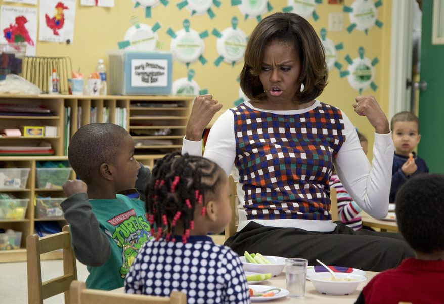 First lady Michelle Obama and a young boy shows off their muscles as they eat healthy snacks during a visit to La Petite Academy in Bowie, Md., Thursday, Feb. 27, 2014, to promote healthy environments and encouraging healthy habits at preschools as part of her Let's Move! Child Care program. (AP Photo/Carolyn Kaster)