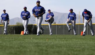 Texas Rangers players stretch before taking in a workout during spring training baseball practice, Sunday, Feb. 23, 2014, in Surprise, Ariz. (AP Photo/Tony Gutierrez)