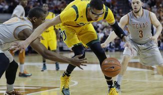 Baylor's Isaiah Austin, center, is pressured by Texas defenders Jonathan Holmes, left, and Javan Felix (3) during the second half of an NCAA college basketball game, Wednesday, Feb. 26, 2014, in Austin, Texas. Texas won 74-69. (AP Photo/Eric Gay)