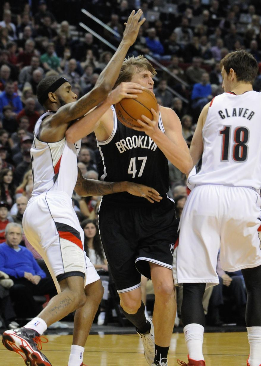 Brooklyn Nets' Andrei Kirilenko (47) drives against Portland Trail Blazers' Will Barton (5) and Victor Claver (18) during the first half of an NBA basketball game in Portland, Ore., Wednesday, Feb. 26, 2014. AP Photo/Greg Wahl-Stephens)