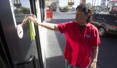 In this Feb. 17, 2014 photo, Rebel store manager Patty Patacsil posts a flier on missing woman Jessie Foster in Las Vegas. Foster, a Canadian, went missing from North Las Vegas in 2006.  (AP Photo/The Las Vegas Sun, Steve Marcus) LAS VEGAS REVIEW-JOURNAL OUT