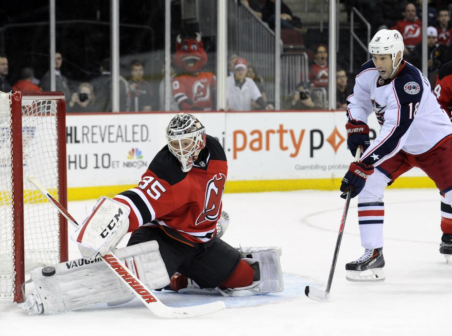New Jersey Devils goaltender Cory Schneider, left, makes a save as Columbus Blue Jackets' R.J. Umberger looks for a rebound during the first period of an NHL hockey game on Thursday, Feb. 27, 2014, in Newark, N.J. (AP Photo/Bill Kostroun)
