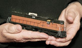This photo taken on Feb. 12, 2014, Mike Bubrick holds a GM locomotive from the early 1950's at his home in Janesville, Wis. Though the scale of his train's are small, Budrick's layout is extremely detailed and quite large, taking up most of the basement. (AP Photo/The Janesville Gazette, Bill Olmsted)