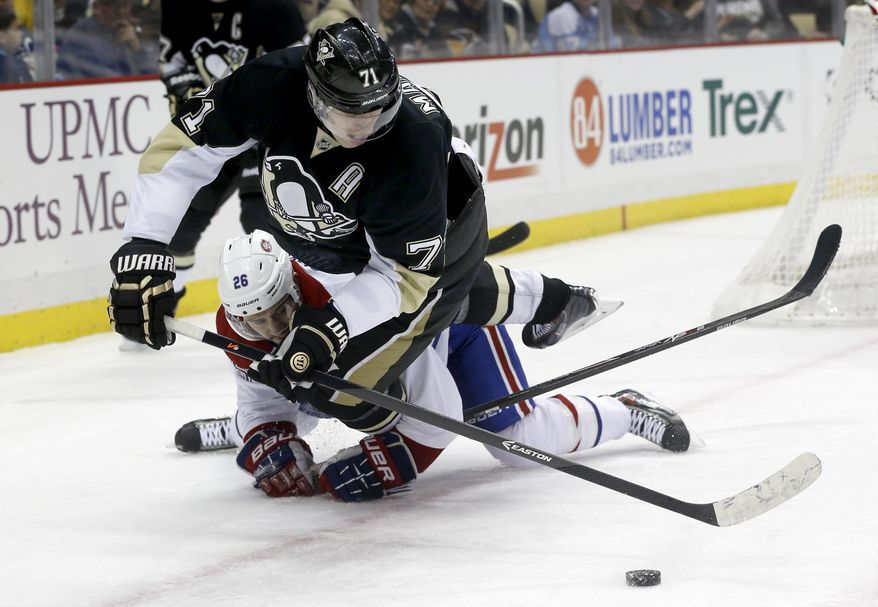 Pittsburgh Penguins' Evgeni Malkin (71), of Russia, tumbles over Montreal Canadiens' Josh Gorges as he goes for the puck during the second period of an NHL hockey game, Thursday, Feb. 27, 2014 in Pittsburgh. (AP Photo/Keith Srakocic)