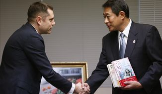 "Israeli Embassy to Japan representative Peleg Lewi, left, shakes hands with Suginami Ward Mayor Ryo Tanaka as he hands over Anne Frank-related books to public libraries at the Suginami Ward Office in Tokyo Thursday, Feb. 27, 2014. The Israeli Embassy is donating 300 books after the recent vandalism of a similar number of such books in their collections. More than 300 books related to Anne Frank, including copies of ""The Dairy of a Young Girl,"" have been found damaged in Tokyo libraries. Suginami was particularly hard hit with 121 books vandalized. (AP Photo/Shizuo Kambayashi)"