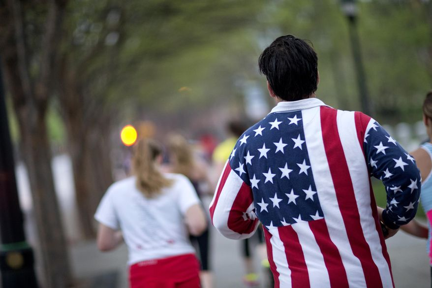 Conn Jackson, of Atlanta, right, wears a shirt decorated with the flag of the United States as he takes part in an organized moment of silence and memorial run to show solidarity with victims of the Boston Marathon bombing, Tuesday, April 16, 2013, in Atlanta. The explosions Monday afternoon killed at least three people and injured more than 140. (AP Photo/David Goldman)