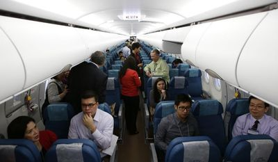 **FILE** Guests chat in the brand new Airbus A321-200 passenger plane of the Philippine Airlines, the country's flag-carrier, during a ceremony at its hangar at the Ninoy Aquino International Airport at suburban Pasay city, south of Manila, Philippines on Aug. 8, 2013. The 199-seater plane is the first acquisition of the Philippine Airlines from the 65 new airplanes, including 20 wide-body A330-300s, procured by PAL over a period of seven years as part of its fleet renewal program. (Associated Press)