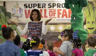 First lady Michelle Obama talks to the kids after they exercised and danced with the Super Sprowtz during a visit to La Petite Academy in Bowie, Md., Thursday, Feb. 27, 2014, to promote healthy environments and encouraging healthy habits at preschools as part of her Let's Move! Child Care program. (AP Photo/Carolyn Kaster)
