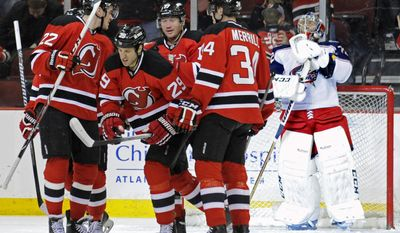 Columbus Blue Jackets goaltender Sergei Bobrovsky, right, reacts as New Jersey Devils' Eric Gelinas (22) Jon Merrill (34), Andrei Loktionov and Ryane Clowe (29) celebrate a goal by Clowe during the first period of an NHL hockey game on Thursday, Feb. 27, 2014, in Newark, N.J. (AP Photo/Bill Kostroun)