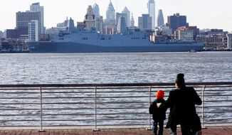 A man and child in Camden, N.J., view the USS Somerset Thursday, Feb. 27, 2014, in Philadelphia. The amphibious transport dock scheduled to be commissioned March 1, is the last of three vessels honoring 9/11 victims and first responders. It joins the USS New York and the USS Arlington. The ship is named for the county where Flight 93 crashed after being hijacked on Sept. 11, 2001. (AP Photo/Matt Rourke)