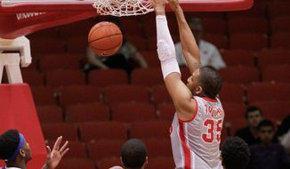 Houston's forward TaShawn Thomas  (35) dunks on Memphis' Geron Johnson (55) during the first half of an NCAA college basketball game, Thursday, Feb. 27, 2014, in Houston. (AP Photo/Bob Levey)