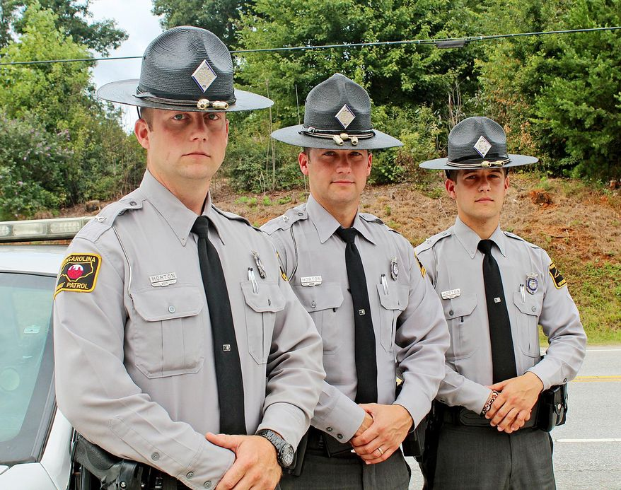 This Aug. 20, 2013 photo shows brothers with the North Carolina Highway Patrol, from left, Nick, John, and Joe Horton in Rutherford County, N.C.  The Hortons are the first and only trio of siblings who have simultaneously worked for the NCHP. (AP Photo/Daily Courier, Alyssa Mulliger)