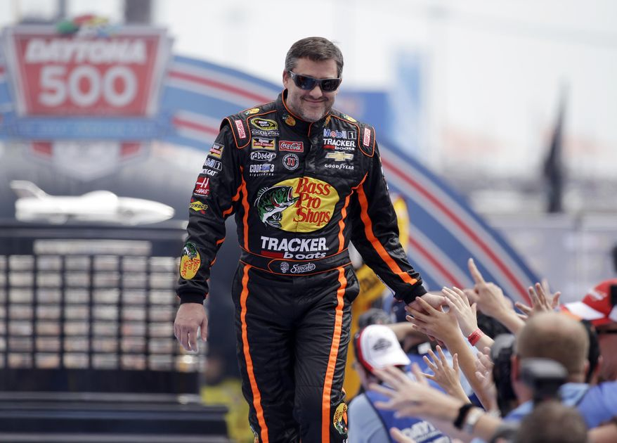 Driver Tony Stewart greets fans as he is introduced before the NASCAR Daytona 500 Sprint Cup series auto race at Daytona International Speedway in Daytona Beach, Fla., Sunday, Feb. 23, 2014. (AP Photo/John Raoux)