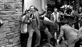 A Secret Service agent shouts after President Ronald Reagan is shot March 30, 1981. (Associated Press)