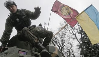 An protester jumps from an army armored vehicle maneuvering in the street outside Parliament in Kiev, Ukraine, Thursday, Feb. 27, 2014, with Ukrainian flag at right, as protests continue against fugitive Ukrainian President Yanukovych.  Ukraine put its police on high alert after dozens of armed pro-Russia men stormed and seized local government buildings in Ukraine's Crimea region early Thursday and raised a Russian flag over a barricade. (AP Photo/Efrem Lukatsky)