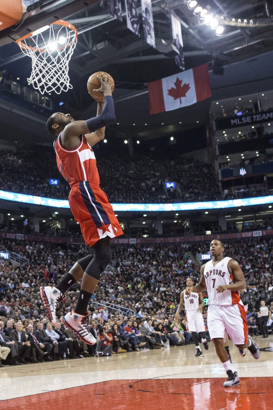 Washington Wizards' John Wall scores as Toronto Raptors' Kyle Lowry looks on during first half NBA basketball action in Toronto, Thursday, Feb. 27, 2014. (AP Photo/The Canadian Press, Chris Young)