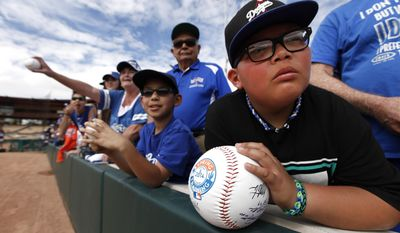 Raymond Rubavcava, 9, of Paris, Calif., waits for autographs before an exhibition baseball game between the Los Angeles Dodgers and the Chicago White Sox in Glendale, Ariz., Friday, Feb. 28, 2014. (AP Photo/Paul Sancya)