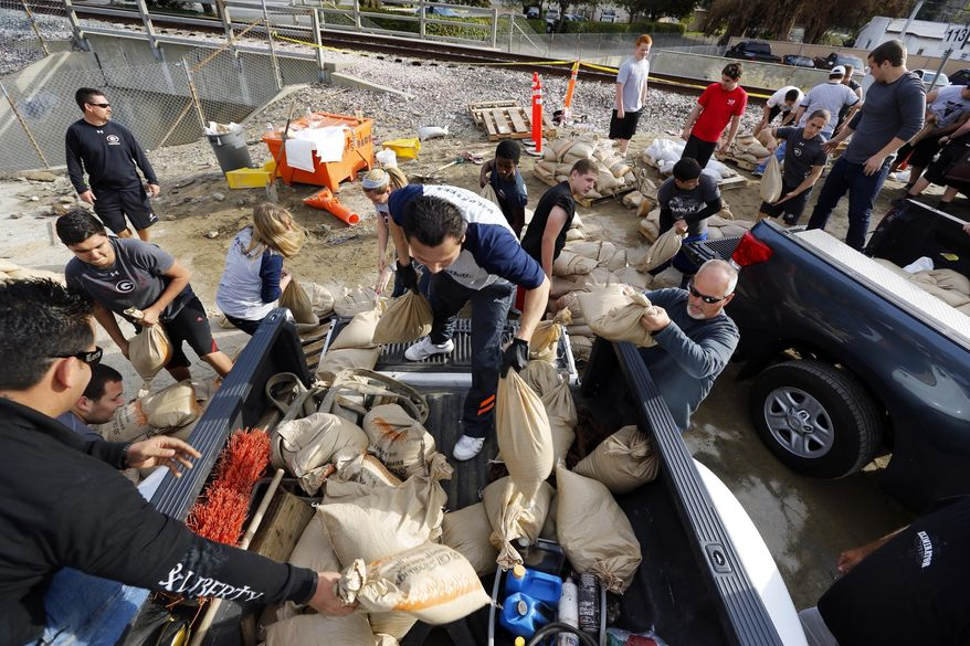 Volunteers fill sandbags in the City of Glendora, Calif., Thursday, Feb. 27, 2014. Residents with the help of their city, prepare for possible flooding. In advance of a powerful Pacific storm, mandatory evacuation orders have been issued for 1,000 homes in Glendora and Azusa, two of Los Angeles' eastern foothill suburbs, which are located beneath nearly 2,000 acres of steep mountain slopes left bare by a January fire. (AP Photo/Damian Dovarganes)