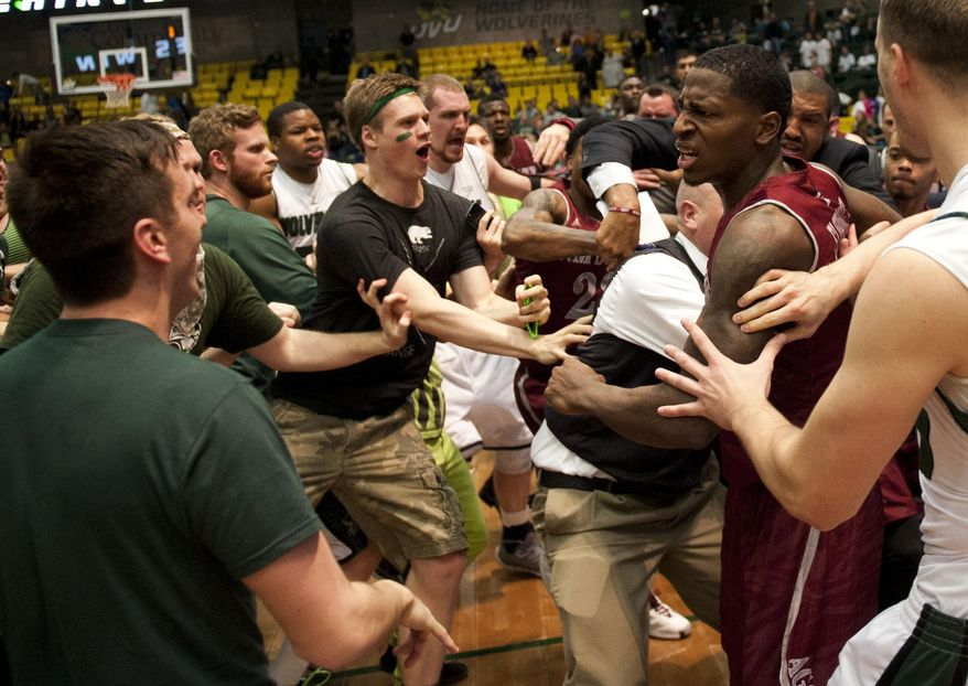 In this Thursday, Feb. 27, 2014 photo, New Mexico State's DK Eldridge, at right in red and white uniform, is held by security during  a brawl involving players and fans who came onto the court when New Mexico State guard K.C. Ross-Miller hurled the ball at Utah Valley's Holton Hunsaker seconds after the Wolverines' 66-61 overtime victory against the Aggies in Orem, Utah.  (AP Photo/The Daily Herald, Grant Hindsley) MANDATORY CREDIT