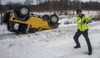 Smitty's Towing and Service Tow Truck driver Kevin Smith, 47, of Burton, Mich., yanks at his pulley cord as he prepares to hook up a rolled over 2004 Jeep Wrangler as he removes it from the side of the road on Thursday, Feb. 27, 2014, on Interstate 69 westbound near the Belsay Road exit in Burton., Mich. (AP Photo/The Flint Journal, Jake May)