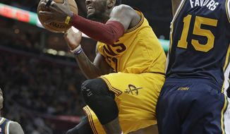 Cleveland Cavaliers' Kyrie Irving, left, jumps to the basket against Utah Jazz's Derrick Favors (15) during the second quarter of an NBA basketball game on Friday, Feb. 28, 2014, in Cleveland. (AP Photo/Tony Dejak)