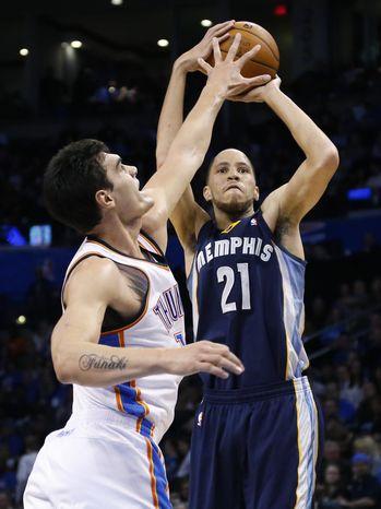 Memphis Grizzlies forward Tayshaun Prince (21) shoots as Oklahoma City Thunder center Steven Adams (12) defends during the second quarter of an NBA basketball game in Oklahoma City, Friday, Feb. 28, 2014. (AP Photo/Sue Ogrocki)