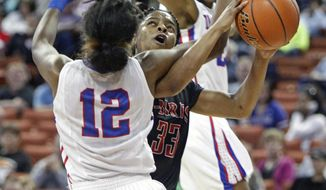 San Antonio Wagner guard Kaelynn Wilson (33) is fouled by Duncanville guard Ariel Atkins (12) during a girls' UIL Class 5A state basketball semifinal on Friday, Feb. 28, 2014, in Austin, Texas. Tasia Foman, behind, looks on. (AP Photo/Michael Thomas)