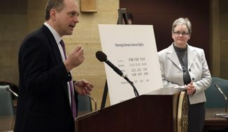 Jim Schowalter, Minnesota Management and Budget Commissioner, presents the state's budget forecast as State Budget Director Margaret Kelly, right, listens, Friday, Feb. 28, 2014 in St. Paul, Minn. Minnesota's projected budget surplus swelled to $1.233 billion, giving lawmakers more leeway to pursue tax cuts and increased spending this session. (AP Photo/Jim Mone)