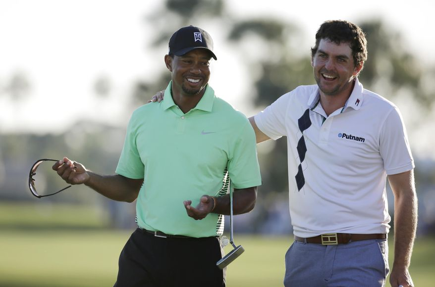 Tiger Woods, left, and Keegan Bradley, right, laugh on the 18th green after completing the second round of the Honda Classic golf tournament, Friday, Feb. 28, 2014, in Palm Beach Gardens, Fla. (AP Photo/Lynne Sladky)