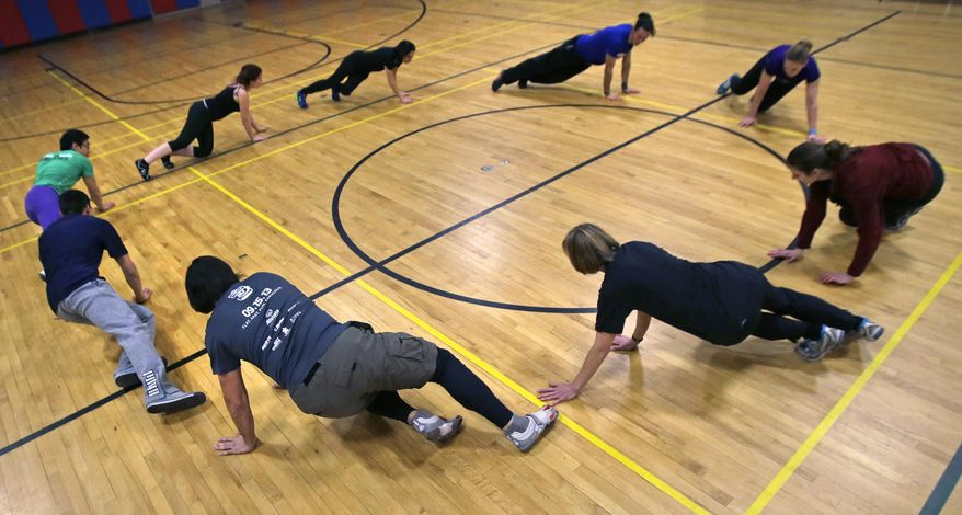 Participants warm up in a circle as a group before a Parkour training class in Brookline, Mass., Wednesday, Jan. 29, 2014. (AP Photo/Charles Krupa)