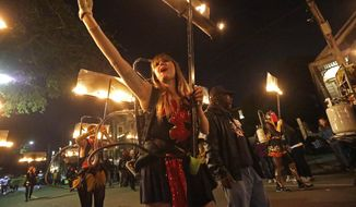 Members of the all-female flambeaux group, called 'Glambeaux,' march in the Krewe of Muses Mardi Gras parade in New Orleans, Thursday, Feb. 27, 2014. (AP Photo/Gerald Herbert)