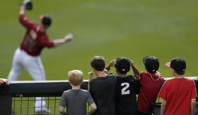 A group of boys watches from the outfield as Arizona Diamondbacks pitcher Jess Todd warms up between innings during a spring training baseball game between the Diamondbacks and the Colorado Rockies on Friday, Feb. 28, 2014, in Scottsdale, Ariz. (AP Photo/Gregory Bull)