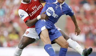 FILE- In this Sept. 11, 2010, file photo, Arsenal's Alexandre Song, left, vies for the ball with Bolton Wanderers' Stuart Holden during an English Premier League soccer match at Arsenal's Emirates Stadium in London. Holden is set to play his first match since being sidelined by another major knee injury last year.  Bolton manager Dougie Freedman says Holden will play Monday, March 3, 2014 for the English team's under-21s against Everton. (AP Photo/Kirsty Wigglesworth, File)