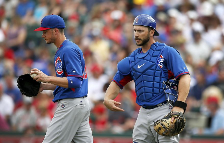Chicago Cubs' Chris Rusin, left, turns back to the pitcher's mound after meeting with George Kottaras during the second inning of a spring training baseball game against the Los Angeles Angels on Friday, Feb. 28, 2014, in Tempe, Ariz. (AP Photo/Ross D. Franklin)