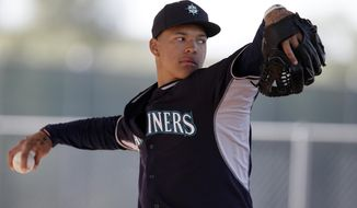 In this Friday, Feb. 20, 2014 photo, Seattle Mariners pitcher Taijuan Walker throws in a bullpen session during baseball spring training in Peoria, Ariz. James Paxton and Walker know the expectations. They understand the Mariners in many ways expect the young pitching prospects to win jobs coming out of spring training and solidify the back end of Seattle's rotation. (AP Photo/Tony Gutierrez)