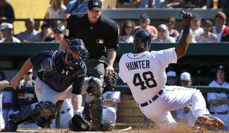 Detroit Tigers' Torii Hunter (48) begins his slide as New York Yankees catcher Brian McCann, left, waits to make the tag at home in front of umpire Andy Fletcher during the third inning of an exhibition spring training baseball game in Lakeland, Fla., Friday, Feb. 28, 2014. Hunter was attempting to score on a single to left field by Tigers' Miguel Cabrera. The Yankees won 7-4.  (AP Photo/Gene J. Puskar)