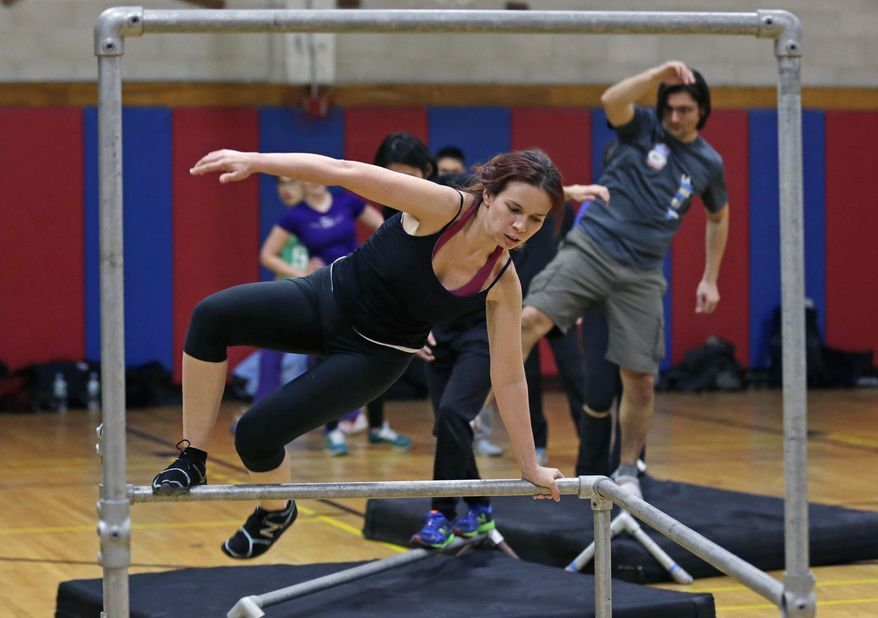 In this Wednesday, Jan. 29, 2014 photo, Jessamyn Hodge, of the South Boston neighborhood of Boston, leaps over a railing during a Parkour training class in Brookline, Mass.(AP Photo/Charles Krupa)