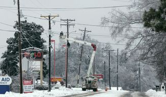 FILE - In this Feb. 13, 2014,  file photo, a utiilites crew works to repair lines off highway 176 in Chapin, S.C., during the worst winter storm in the state in a decade. A state emergency official said Friday, Feb. 28, 2014 that, while figures are still being compiled, damage from the storm will likely qualify sections of the state for designation as a federal disaster area - the first such designation in almost a decade. (AP Photo/Mary Ann Chastain, File)