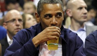 **FILE**  In this July 16, 2012 file photo, President Barack Obama sips his beer as he watches Team USA and Brazil during the first half of an Olympic men's exhibition basketball game, in Washington. (AP Photo/Alex Brandon, File)
