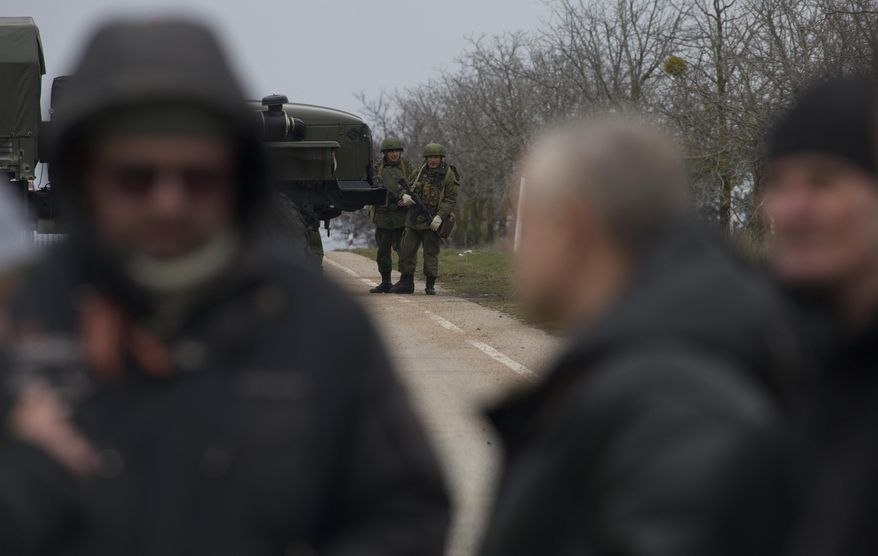Unidentified gunmen block the road toward the military airport at the Black Sea port of Sevastopol in Crimea, Ukraine, Friday, Feb. 28, 2014, as local residents are seen, in foreground. Russian troops took control of the two main airports in the strategic peninsula of Crimea, Ukraine's interior minister charged Friday, as the country asked the U.N. Security Council to intervene in the escalating conflict. Russian state media said Russian forces in Crimea denied involvement. No violence was reported at the civilian airport in Crimea's capital of Simferopol or at the military airport in the Black Sea port of Sevastopol, also part of Crimea. At the Simferopol airport, a man claiming to speak for the camouflage-clad forces patrolling the airport described them as Crimean militiamen. (AP Photo/Ivan Sekretarev)