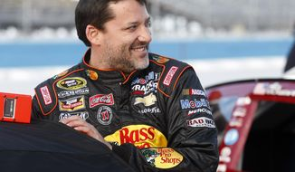 Tony Stewart (14) climbs into his car before qualifying for Sunday's NASCAR Sprint Cup Series auto race on Friday, Feb. 28, 2014, in Avondale, Ariz. (AP Photo/Rick Scuteri)
