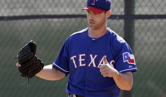 In this photo taken Feb. 23, 2014, Texas Rangers' Neal Cotts gives a thumbs-up after throwing in the bullpen during spring training baseball practice in Surprise, Ariz. Cotts received an unexpected call from the Rangers, and last season made a record-setting comeback. (AP Photo/Tony Gutierrez)