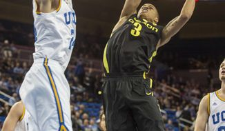 Oregon guard Joseph Young, right, goes up for a lay up against UCLA forward Travis Wear in the first half of an NCAA college basketball game Thursday, Feb. 27, 2014, in Los Angeles. (AP Photo/Ringo H.W. Chiu)