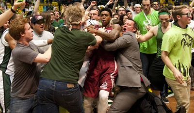 In this Thursday, Feb. 27, 2014 photo, New Mexico State's Daniel Mullings, at center in red and white jersey, is involved in a brawl involving players and fans who came onto the court when New Mexico State guard K.C. Ross-Miller hurled the ball at Utah Valley's Holton Hunsaker seconds after the Wolverines' 66-61 overtime victory against the Aggies in Orem, Utah.  (AP Photo/The Daily Herald, Grant Hindsley) MANDATORY CREDIT
