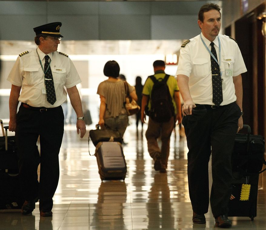 FILE - In this  Nov. 30, 2011, file photo, two pilots from Cathay Pacific walk in the Hong Kong International Airport in Hong Kong. The U.S. airline industry will need to hire 1,900 to 4,500 new pilots annually over the next 10 years due to an expected surge in retirements of pilots reaching age 65 and increased demand for air travel, the Government Accountability Office said in the report obtained late Thursday, Feb. 27, 2014. (AP Photo/Vincent Yu, File)